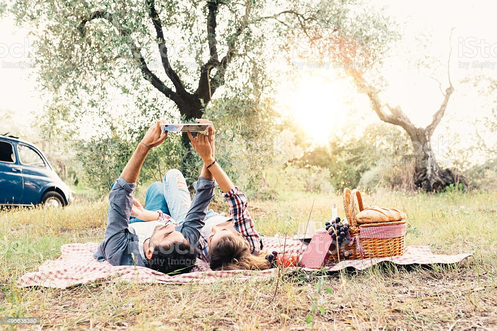 Young Couple Using Tablet During Picnic Outdoor stock photo