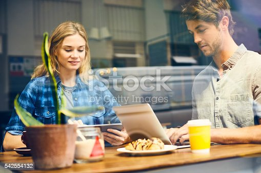 Young couple using technologies at table. Man and woman are sitting in cafe seen through glass window. They are in casuals at trendy coffee shop.