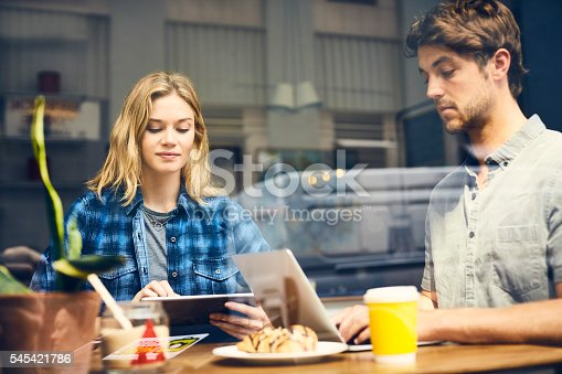 Young man and woman using technologies at table. Couple are sitting in cafe seen through glass window. They are wearing trendy casuals in coffee shop.