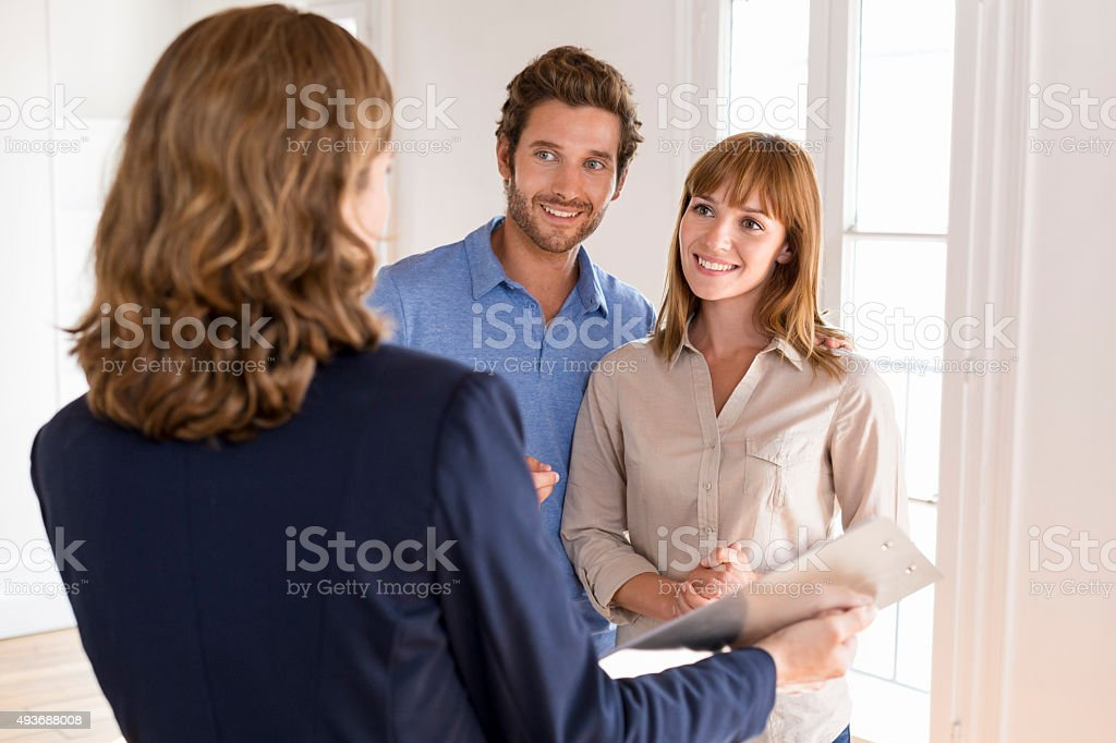Young couple visiting apartment with real estate agent stock photo