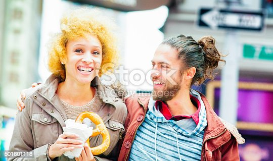 Young couple visiting New york City with big smiles on. The female is holding a pretzel and a coffee while telling a story to her attentive boyfriend.