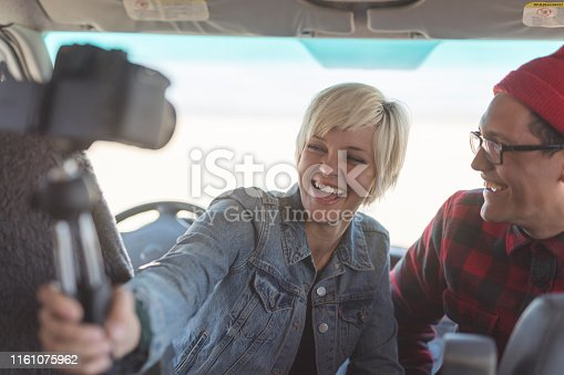 A cute young interracial couple film a segment for their vlog inside their van. She is holding a camera on a selfie stick while she sits in the driver's seat.They are both smiling and looking into the camera she's holding and filming themselves with.