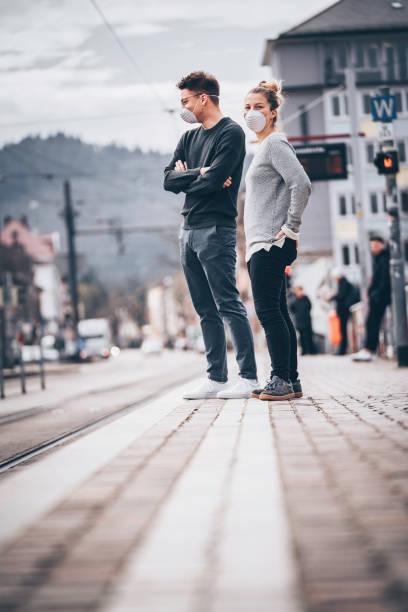 jong paar wacht op trein om in spookstad aan te komen - zwarte spijkerbroek stockfoto's en -beelden