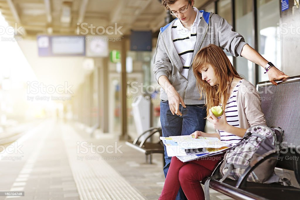 young couple waiting for the train, looking at map royalty-free stock photo