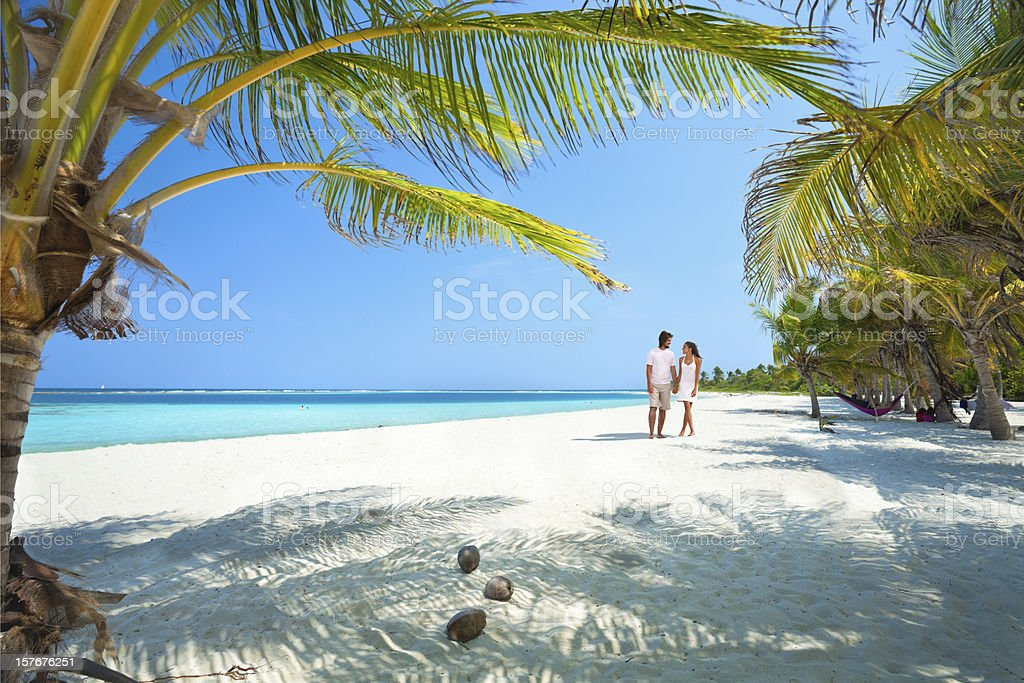 Young couple walking along a lonely Tropical island beach stock photo