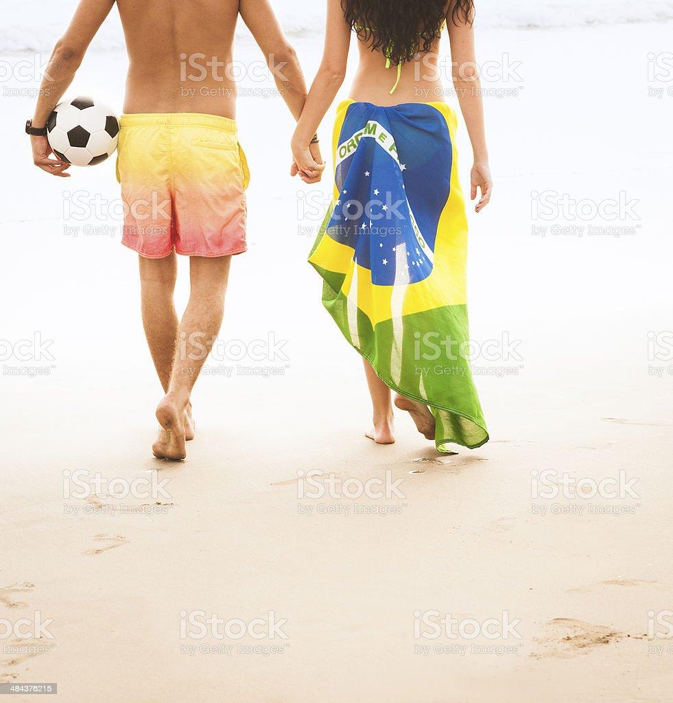Casal jovem caminhando ao longo da praia com o futebol, bandeira do Brasil - foto de acervo