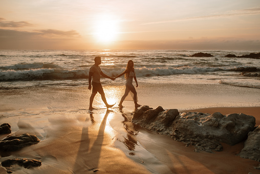 Young couple  walking and holding hands at a beach at sunset