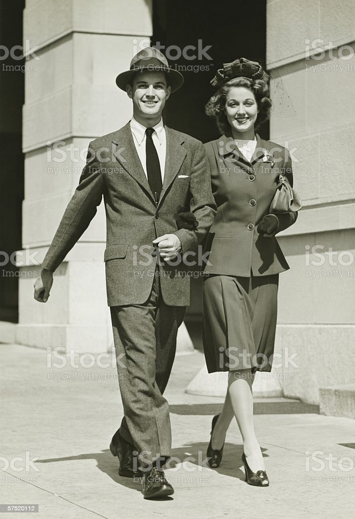 Young couple walking arm in arm on sidewalk, (B&W) royalty-free stock photo