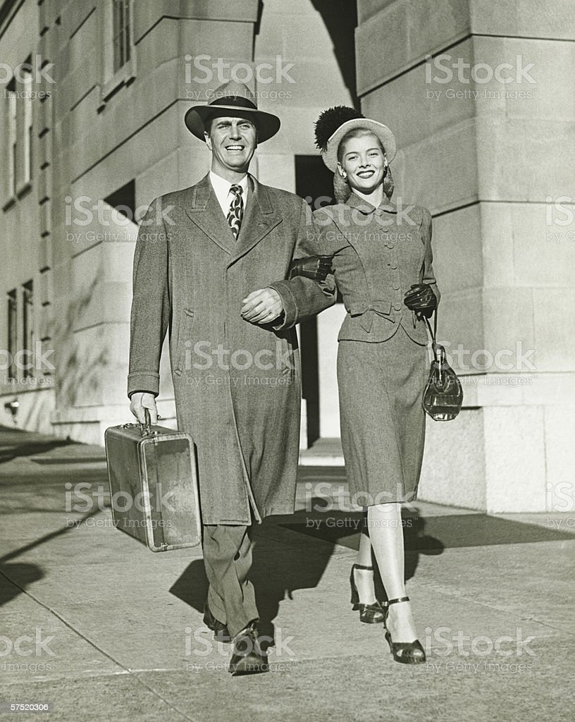 Young couple walking arm in arm on sidewalk, (B&W) stock photo