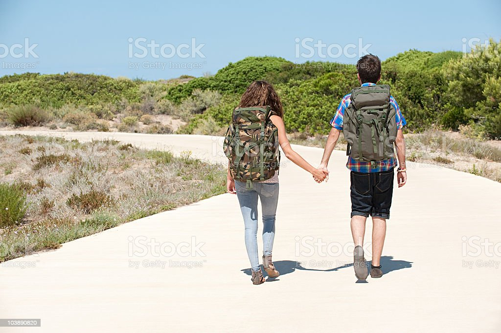 Young couple walking down rural road, rear view royalty-free stock photo