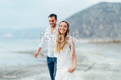 A young couple is walking happily by the water hand in hand.