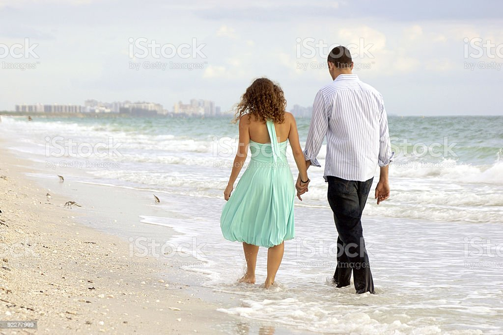 young couple walking hand in hand on the beach thier stock photo