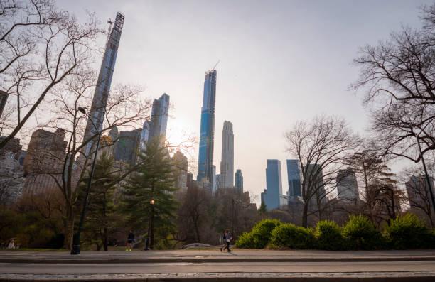 Junges Paar zu Fuß vor Manhattan Skyline auf Central Park verlassen wegen Coronavirus Ausbruch. – Foto