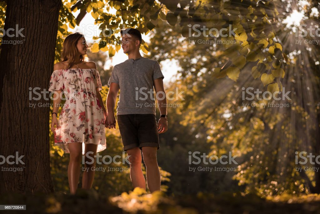 Young couple walking in nature and talking to each other - Royalty-free Adult Stock Photo