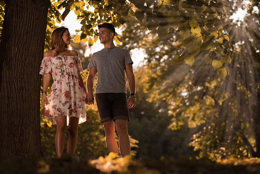 Young Couple Walking In Nature And Talking To Each Other Stock Photo - Download Image Now
