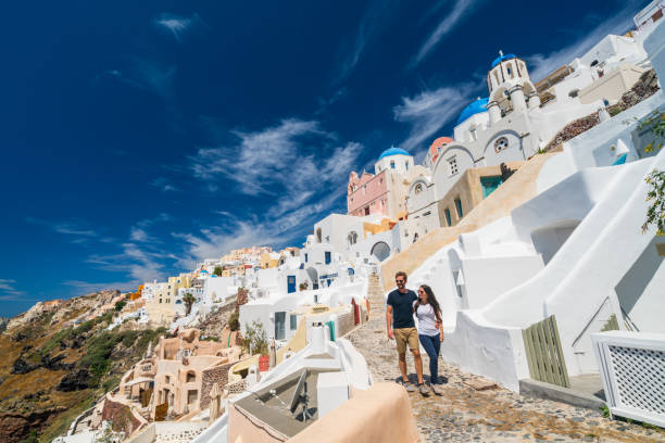 young couple walking in oia santorini - santorini stock photos and pictures