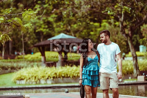 Young couple walking in public park in front of Petronas towers in Kuala Lumpur.