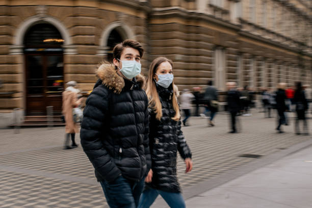 Young couple walking in the city wearing protective face masks stock photo