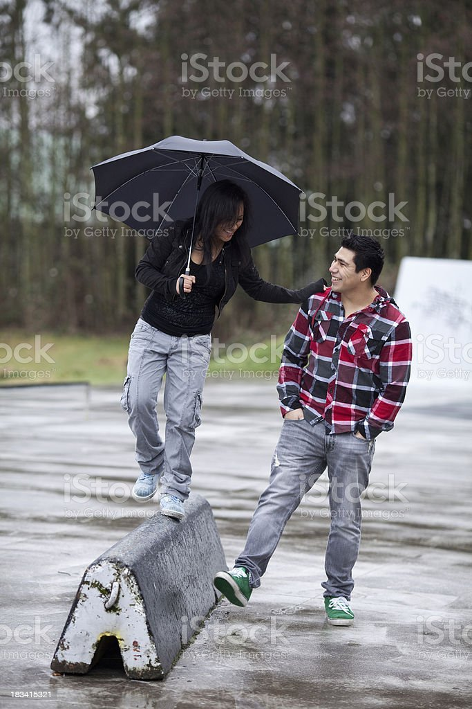 Young couple walking in the rain with an umbrella royalty-free stock photo