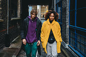 Young couple walking in the street. They are wearing colorful clothes and looking at camera. Shoreditch, London.