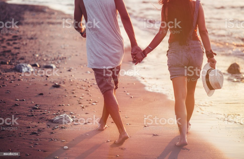 Young couple walking on beach and holding hands at sunset stock photo