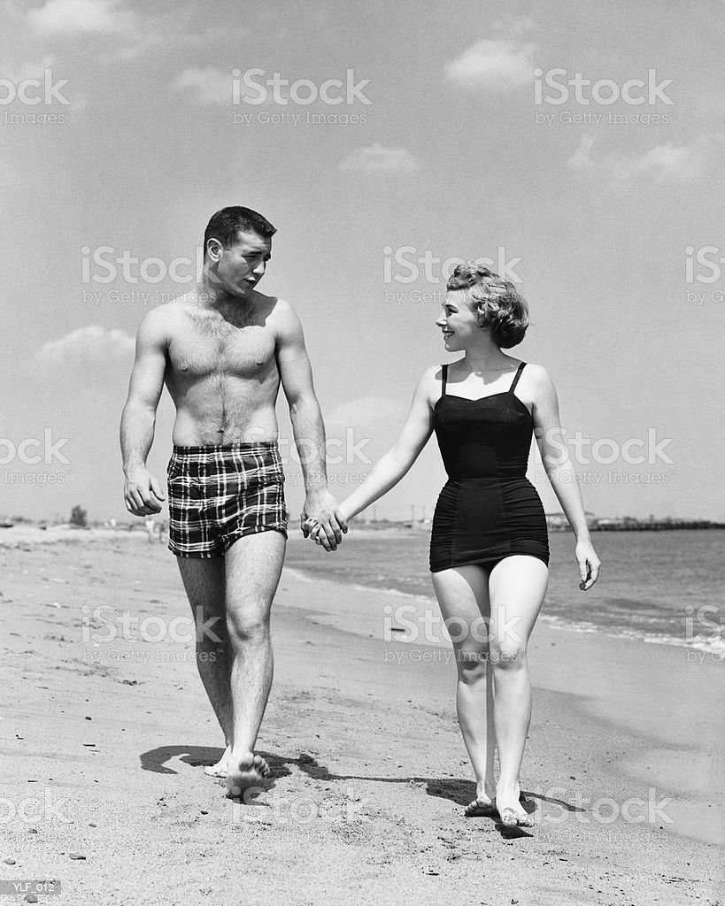 Young couple walking on beach royalty free stockfoto