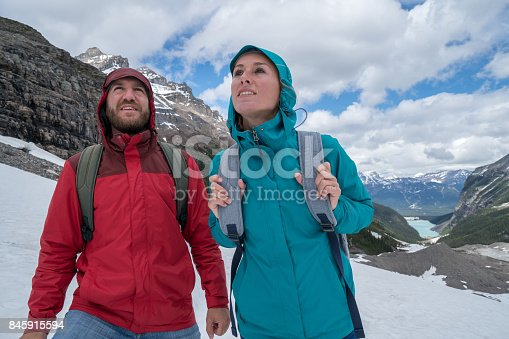 Two young adults hiking on glacier in Springtime.