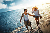 Closeup front view of mid 20's couple walking on a beach on a beautiful summer sunset. They are having fun and enjoying their vacation.