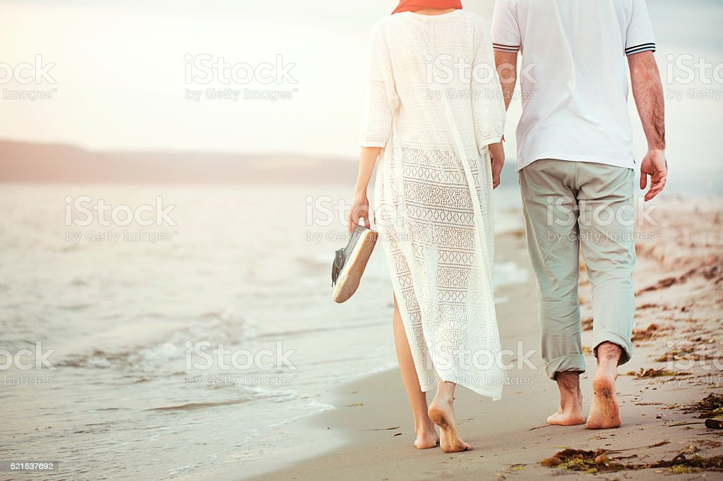 Young Couple Walking On The Beach stock photo