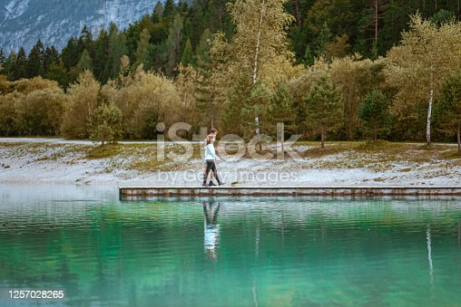 Young caucasian couple in sport clothes walking on the pier by the lake jasna in Kranjska Gora.