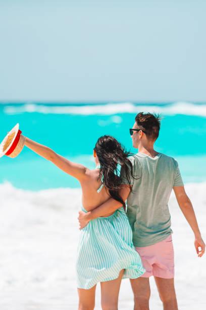 Junges Paar zu Fuß am tropischen Strand mit weißem Sand und türkisfarbenem Meerwasser auf Antigua Insel in der Karibik – Foto