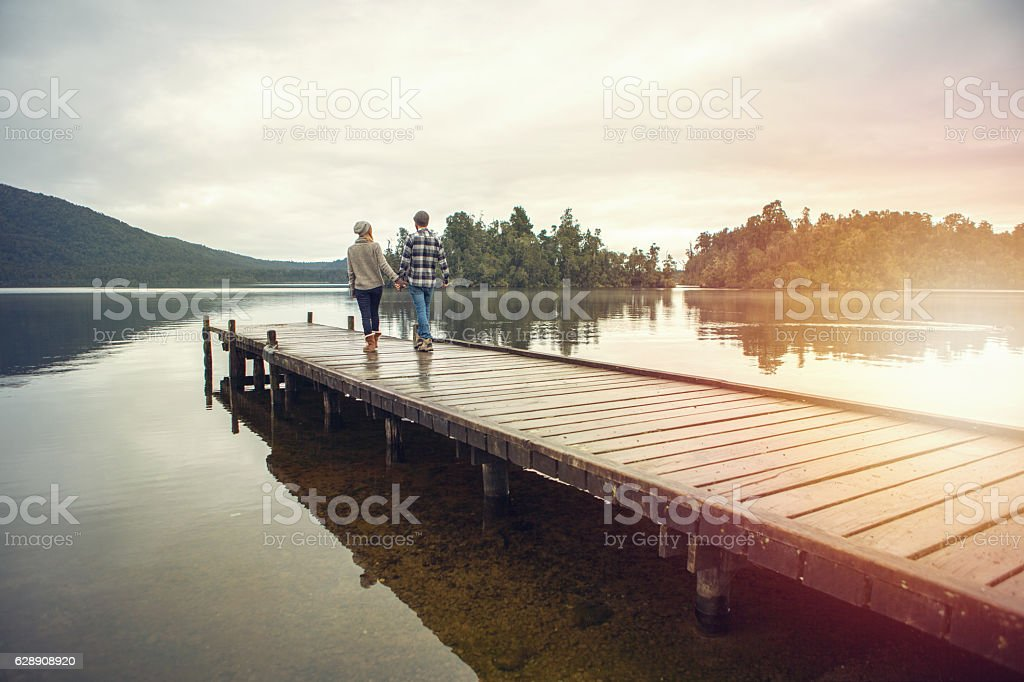 Young couple walking on wooden pier above lake – Foto
