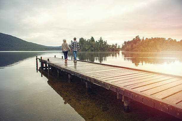 Young couple walking on wooden pier above lake - Photo