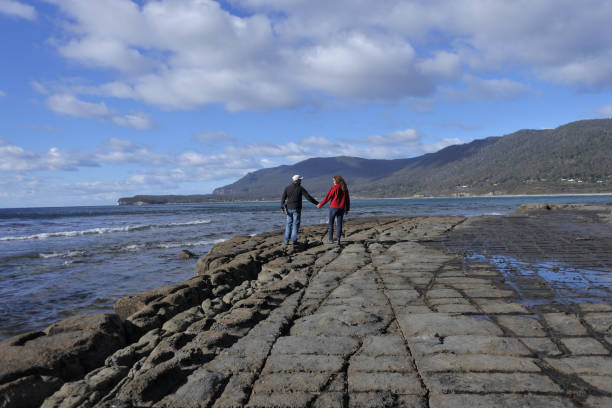 Young couple walking over the Tessellated Pavement in Tasman Peninsula Tasmania Australia stock photo