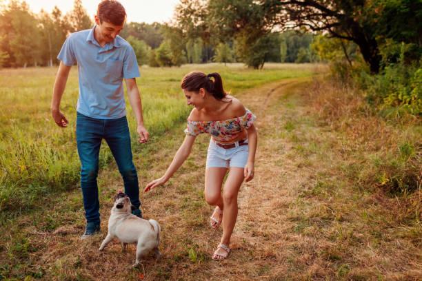 Young couple walking pug dog in autumn forest happy puppy running picture id1037102790?b=1&k=6&m=1037102790&s=612x612&w=0&h=2qzthlbwcacxwapl2kwt pteozqesra3qmesukidlj8=