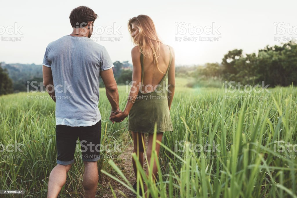 Young couple walking through grassy road stock photo
