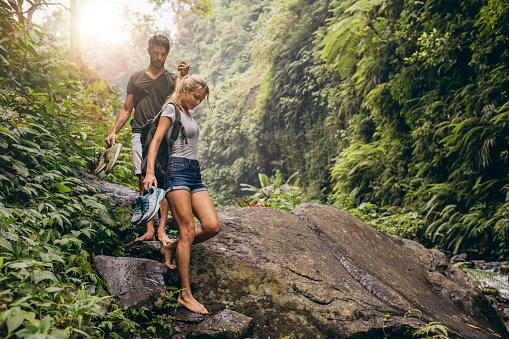 Young couple walking through the mountain trail.