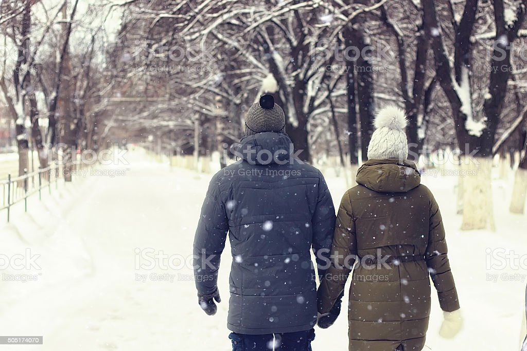young couple walking winter stock photo