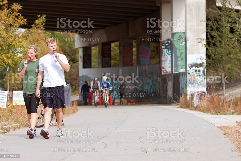 Young Couple Walks And Eats Popsicles In Urban Setting stock photo