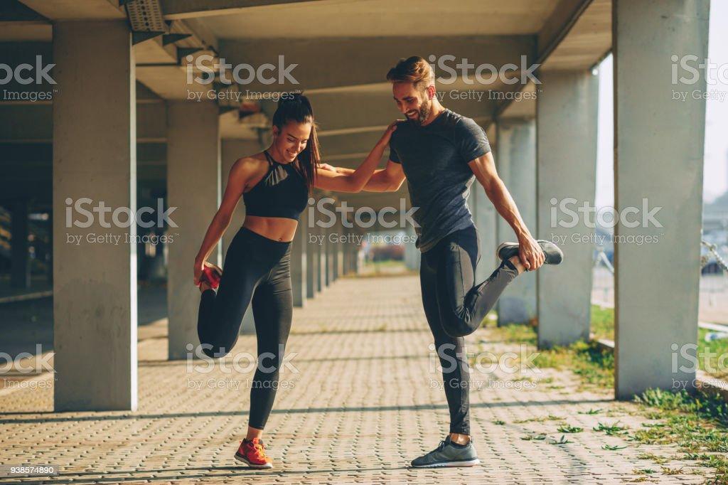 Junges Paar im urbanen Umfeld Aufwärmen vor dem Joggen – Foto