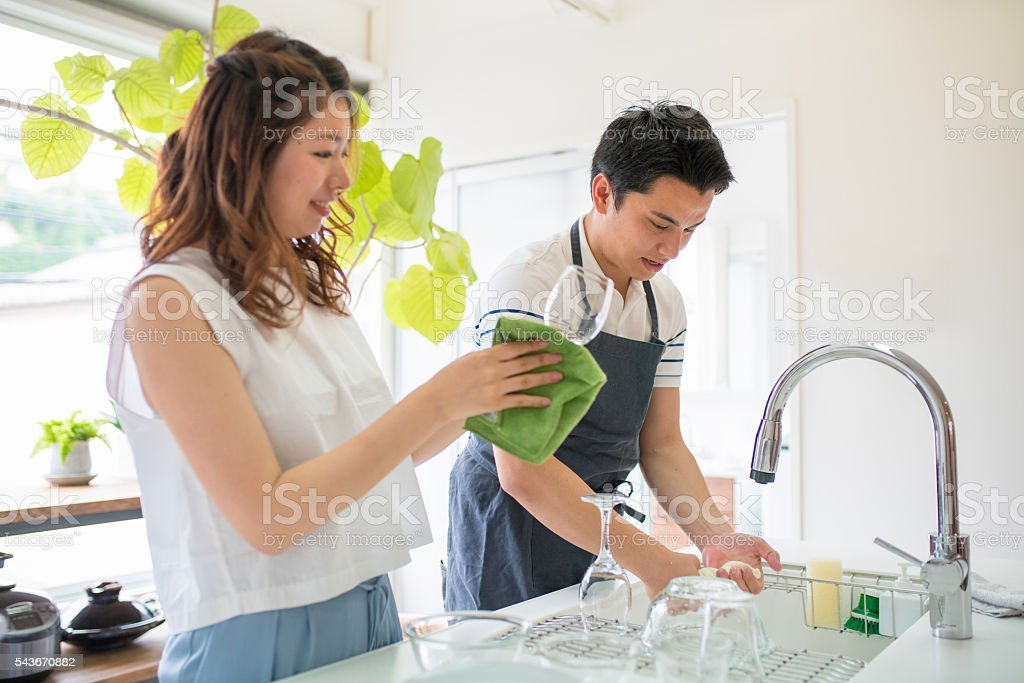 Young couple washing dishes together in the kitchen stock photo