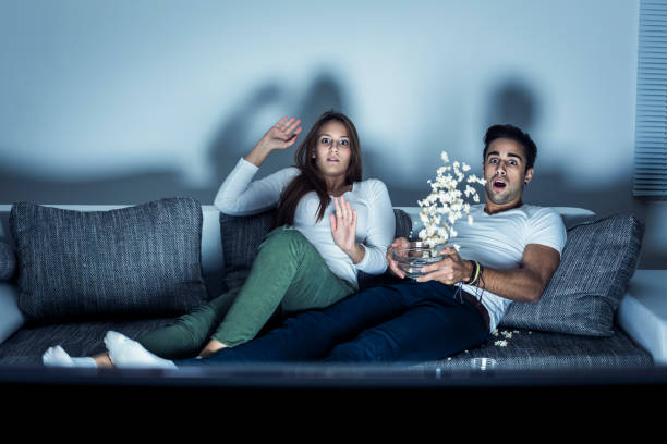 Young couple watching a horror movie stock photo