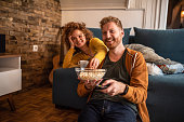 istock Young couple watching a movie at home. 1284280647