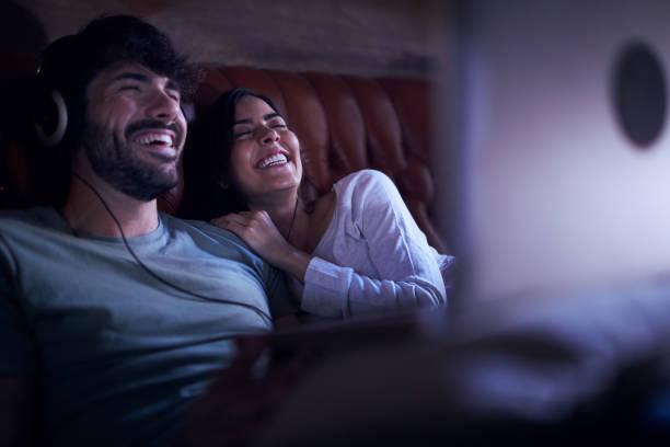 genç bir çift bir dizüstü bilgisayar bir film izlerken. - bilgisayardan yükleme stok fotoğraflar ve resimler