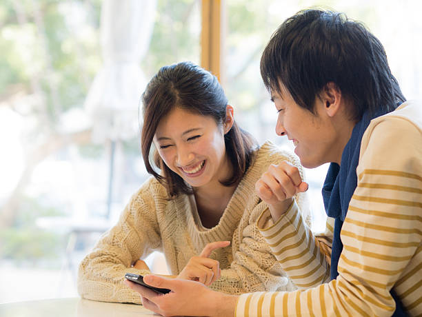 Young couple watching any contents on a smartphone A young couple watches any contents on a smartphone. A young man bas a smartphone on his hand. japanese ethnicity stock pictures, royalty-free photos & images