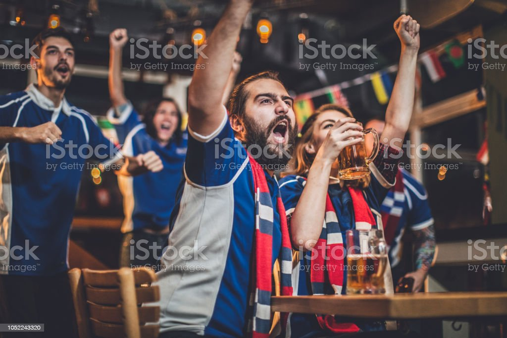 Couple cheering with beer in a pub with group of friends