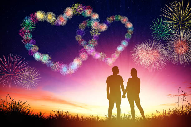 young couple watching heart shape fireworks on hill - fourth of july zdjęcia i obrazy z banku zdjęć