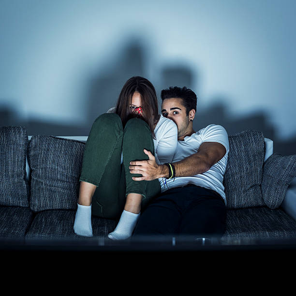 Young couple watching horror movie stock photo