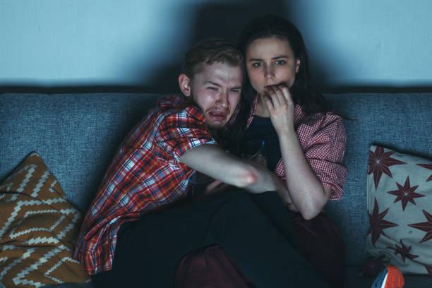 junges paar beobachten horrorfilm - mädchen night snacks stock-fotos und bilder