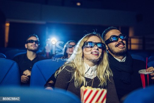 187095683 istock photo Young couple watching movie 855628842